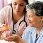 Hispanic nurse helping senior woman with medication